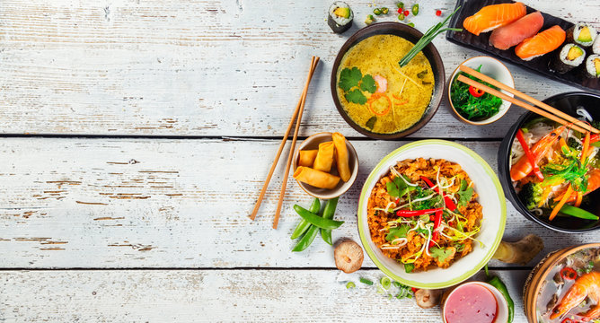 Asian food served on wooden table, top view, space for text