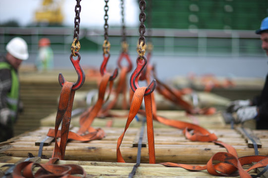Chains and hooks hoist with slings for loading timber on board the vessel
