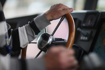 The hands of the captain and a steering wheel boat port services