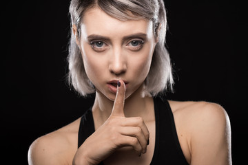 portrait of woman in bodysuit showing silence sign on black