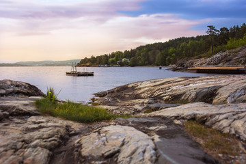 Beautiful Norwegian water scape with a rocky coast, boat, pine forest and blue sky at sunset