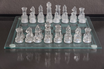 Setup of the start of chess game on a glass chessboard