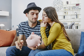 Couple in furniture store demolishing piggy bank
