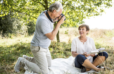 Happy senior man taking picture of his wife in meadow