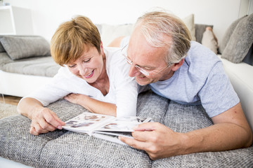 Senior couple at home lying on couch looking at photo album