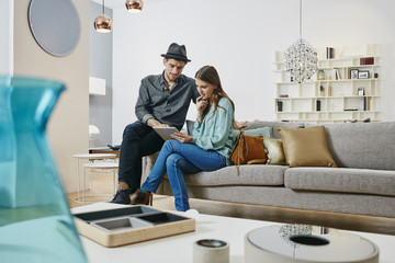 Couple choosing furniture in shop, using digital tablet