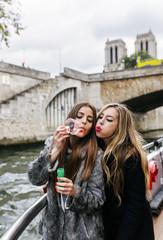 Paris, France, portrait of two friends blowing soap bubbles together