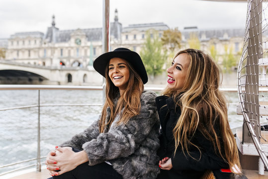 Paris, France, two laughing tourists taking a cruise on Seine River