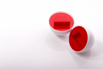 Plastic egg developmental puzzle red with a trapezoid shape on white background.