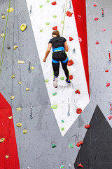 Woman or Girl exercises on indoor rock climber wall hanging on a rope