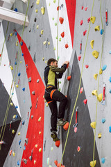young caucasian man training at artificial rock climbing indoors