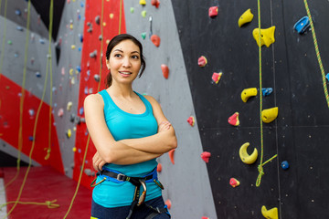 Young woman exercises on indoor rock climber