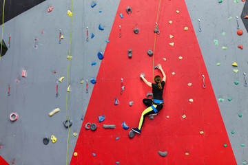 Concentrated sports woman climbing up the wall at indoor gym