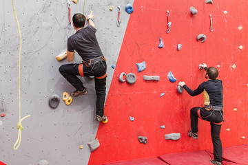 Two climbers compete in a friendly match in the climbing gym indoors