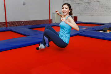 Jumping young woman on a trampoline in amusement park