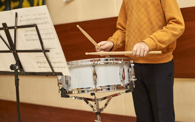 Young musician playing drum in school