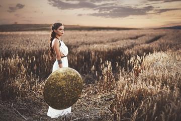 Brunette wearing in dress like greece style holding shield. Wall mural