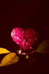 Pink heart with highlights and leaves on a dark background.