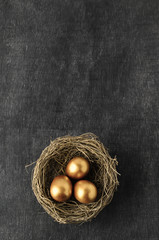 Overhead of Nest containing Three Gold Eggs on Chalkboard Background