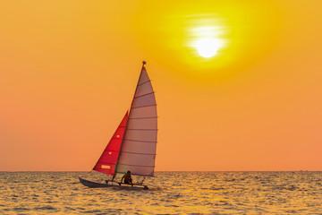 sailing boat with orange sky