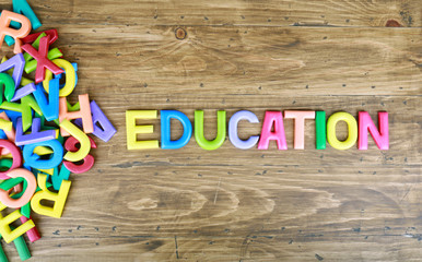 "The colorful word ""EDUCATION"" next to a pile of other letters over the old wood board"