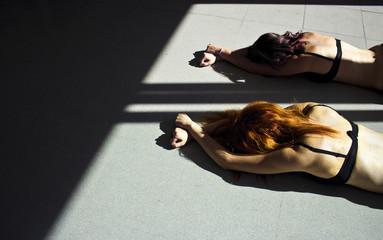 Women on the floor with hands tied