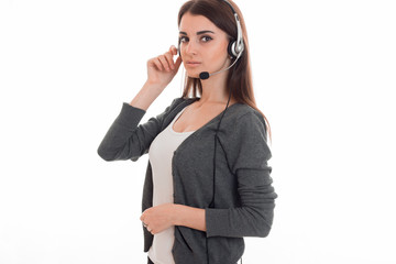 young pretty brunette business woman with headphones and microphone looking at the camera isolated on white background