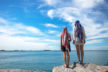 Two traveler young women seeing the beautiful beach and blue sky, so happy and relax