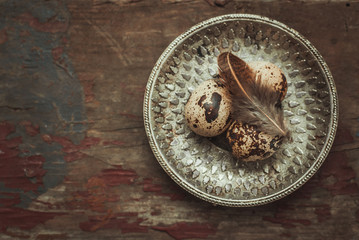 Three fresh raw quail eggs on vintage metal plate on a rustic wooden background. dark and moody toned picture. top view and space for text