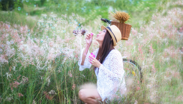 Woman blowing bubbles in meadow. travel and sunset, soft focus