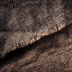 Old wooden  table with sack cloth  in dark interior with copy space. Burlap texture.