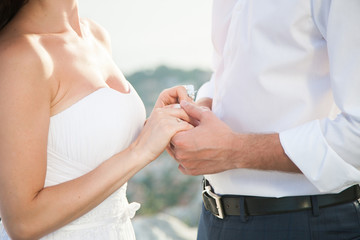Newlyweds are holding hands on wedding ceremony on sunset during wedding vows on background of sea, mountains. The bride is dressed in classic white wedding dress, the groom is wearing in white shirt.
