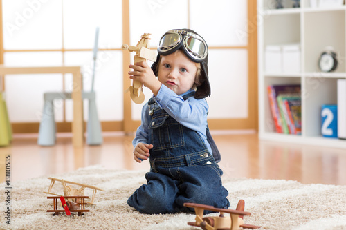 Pilot aviator child plays with wooden toy airplanes on floor in his room