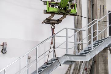 Folk lift transporting metal staircase