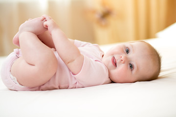 Funny smiling baby infant girl playing with her feet