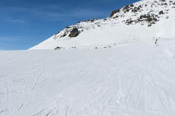 Skiers on a piste in alpine ski resort