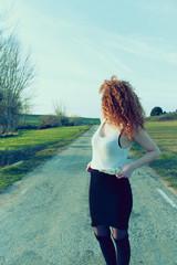 Chica pelirroja con el rostro tapado en mitad de una carretera rural