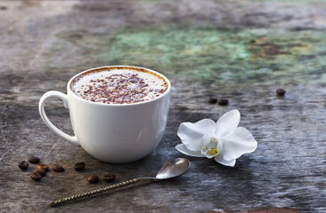 A cup of hot coffee and orchid flower on the wooden background. Traditional drink cappuccino or cocoa Wooden background Orchid flower