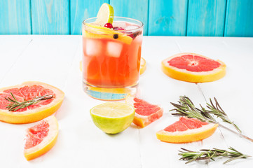 Refreshing homemade grapefruit and rosemary cocktail on white wooden table