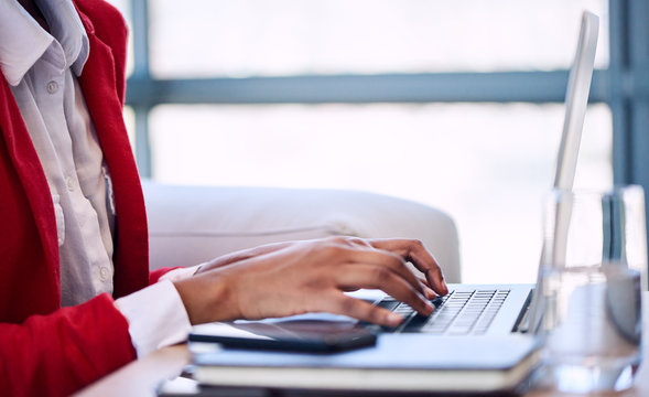 Generic image of a black woman's hand busy typing on a modern notebook with her head cropped out of the image while wearing a white shirt and red blazer as well as large windows in the background.