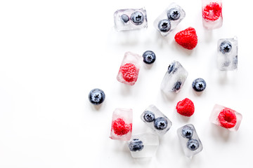 ice cubes with fresh berries on white background top view mock up