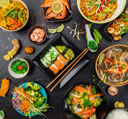 Asian food served on black stone, top view