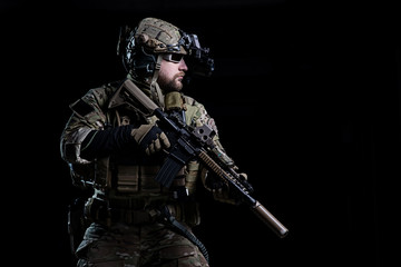 Spec ops soldier SWAT/Special Forces soldier in helmet with night vision device and rifle on dark background