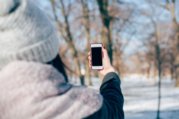 Woman taking a photo of snowy trees