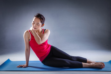 Unhappy young woman sitting on the mat, grabbing nape, unable to start yoga work out because of sport injury, feeling pain.