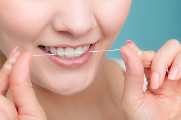 Woman smiling with dental floss.