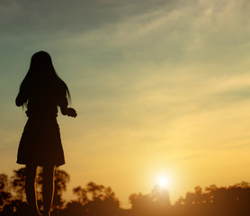 Silhouette of woman praying over beautiful sky sunset background