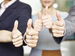 business people showing thumb-up signs