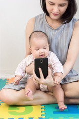 Portrait of a little adorable infant baby girl sitting on mother lap on colorful eva foam and listening to smart phone