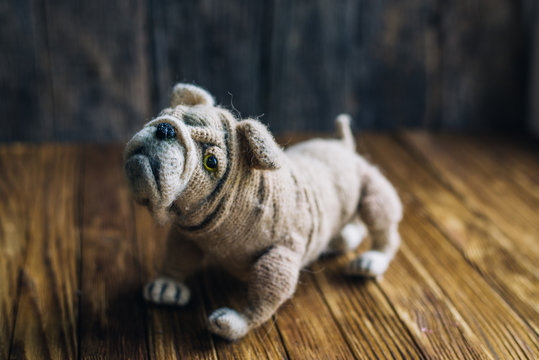 Knitted dog bulldog isolated on wooden background.